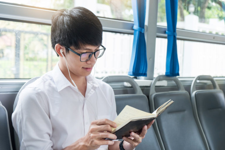 man reading a book in public transportation